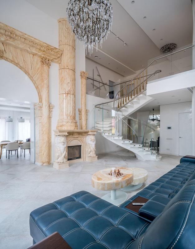 Фото интерьера дома, вид на двухуровневую гостиную с колоннами и лестницей