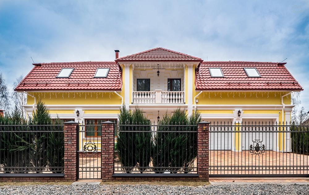 Фасад двухэтажного дома за забором